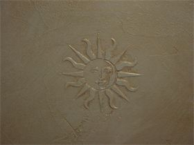 : This sun emplem was imposed in the plaster and the gold qlaze highlites its features